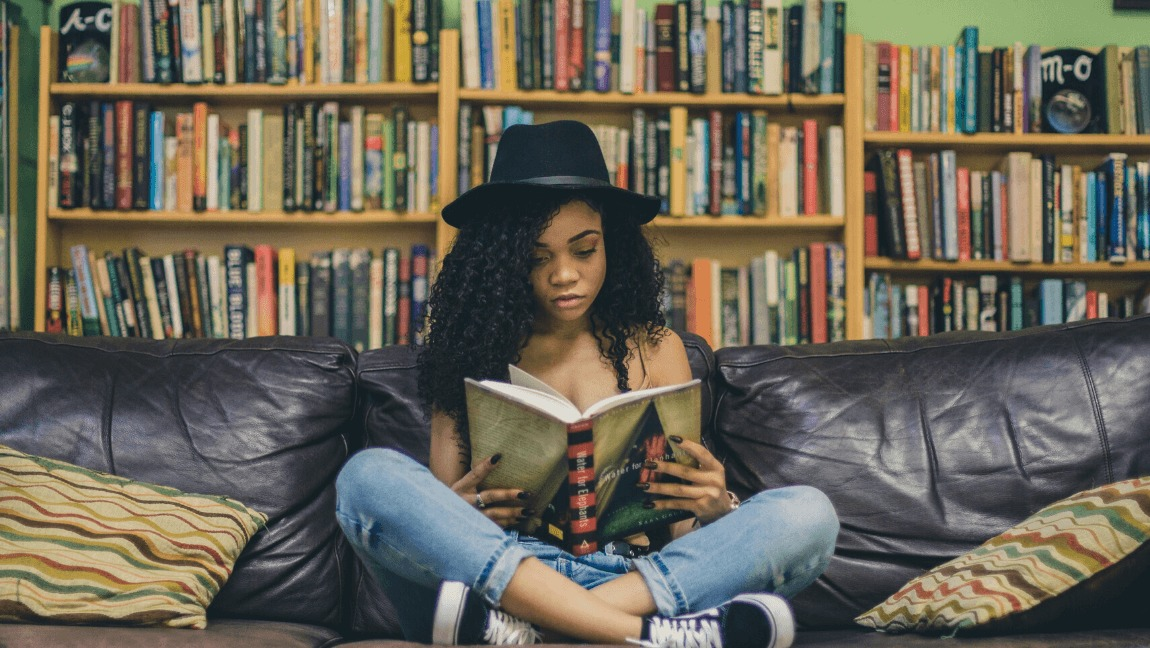 A curly-haired girl is sitting cross-legged on a sofa, while reading, in a library.