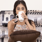 A dark-haired woman is is sipping from a mug while flipping through TV channels.