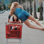 A woman pushes another woman, seated in a red shopping cart, away from the camera and down a road lined with trees. The woman pushing the cart is jumping in the air, with her legs swung to the side.