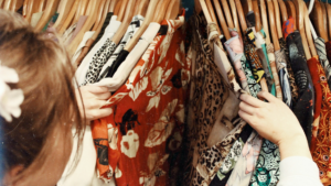 A woman sifts through a rack of clothes.