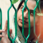 [Image description: Woman holds onto the fence, looking to the camera.] Photo by Khadija Yousaf on Unsplash