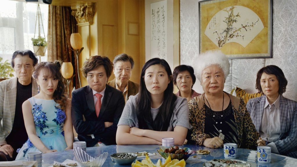An Asian family sitting together on a dining table looking in front.
