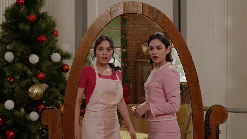 Two identical women - one in an apron, the other in a business-casual ensemble - stare in shock at each others reflection.