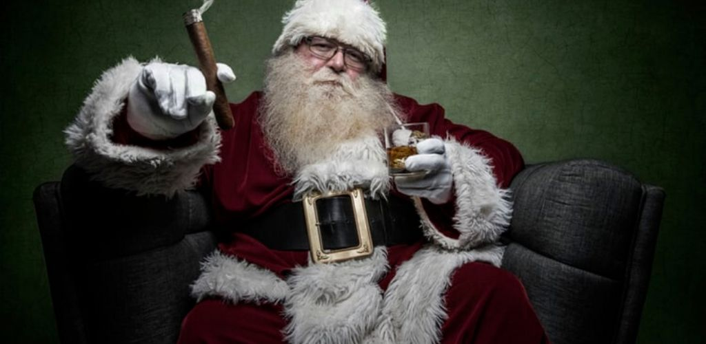 [Image description: Santa Claus sits, holding a lit cigar and a glass of whiskey] Via Unsplash