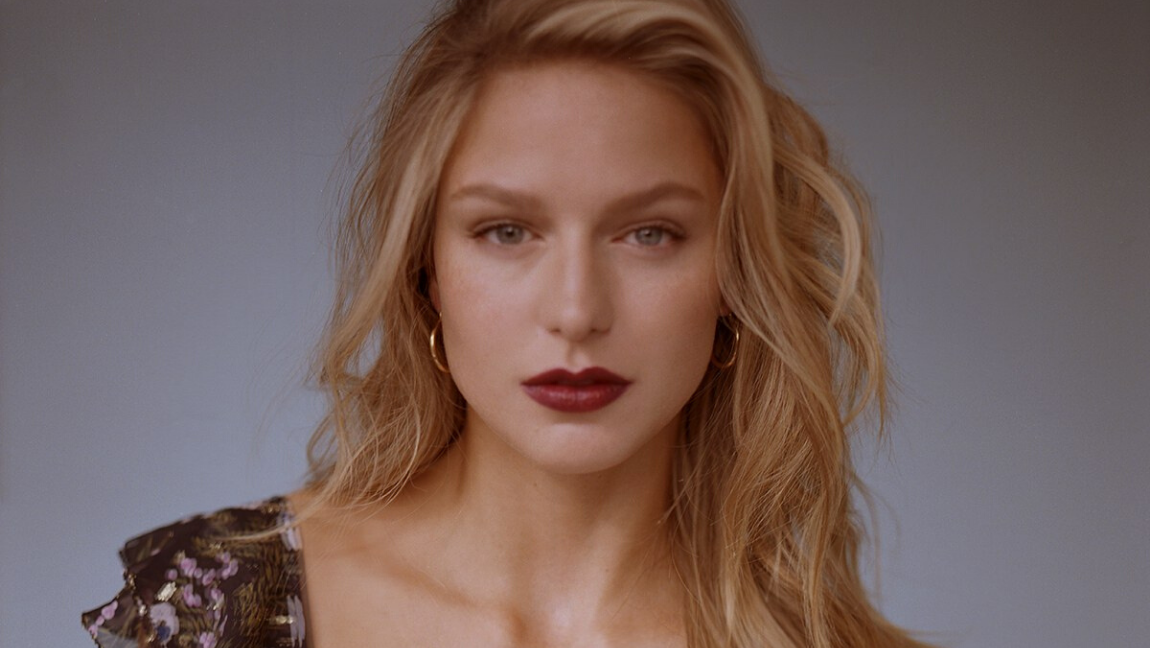 Actress Melissa Benoist wearing a dark lip with hair down.