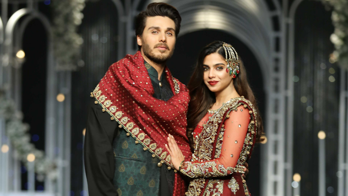 A Pakistani couple showstopping for a local designer in Bridal Couture Week wearing complimenting deep red bridal attires.