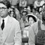 A black-and-white still of a man in a suit seated next to a man in overalls in a courtroom.