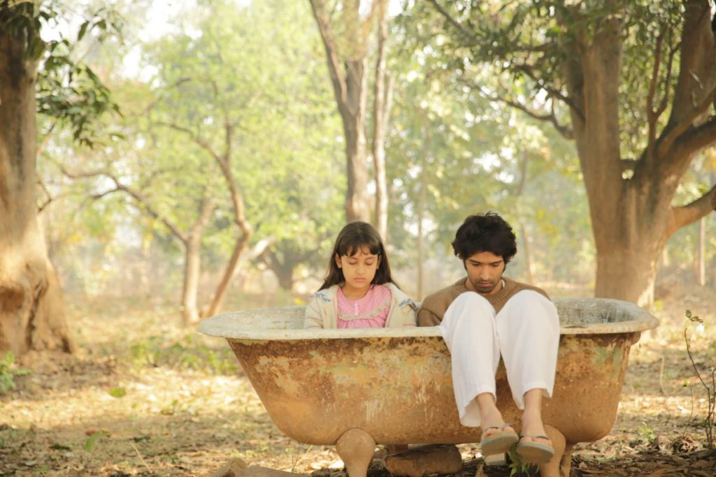 A little girl and a young man sitting in an empty tub outside in the woods.