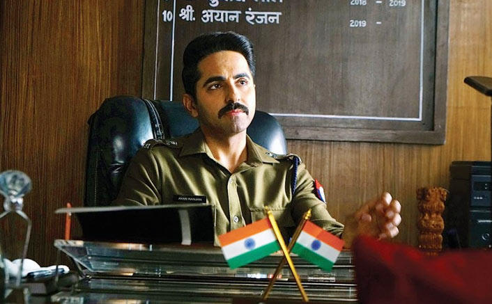 A dark-haired man with a mustache is sitting behind a desk which bears tiny Indian flags