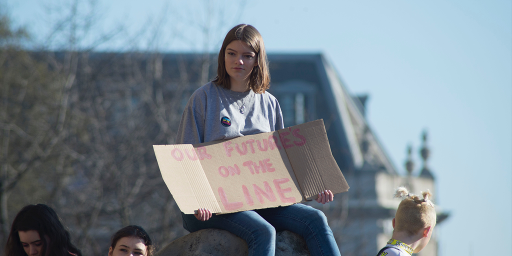 "A girl sitting on top of a platform holding a sign which says ""Our future's on the line""."