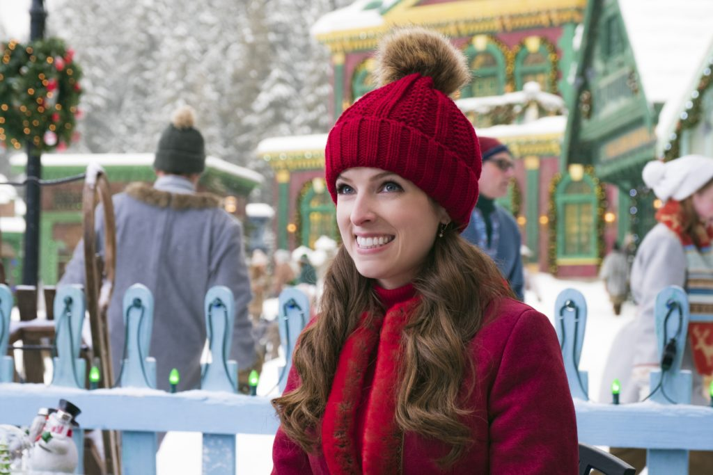 A brunette woman smiles ecstatically. She's in a red coat, red scarf, and red beanie.
