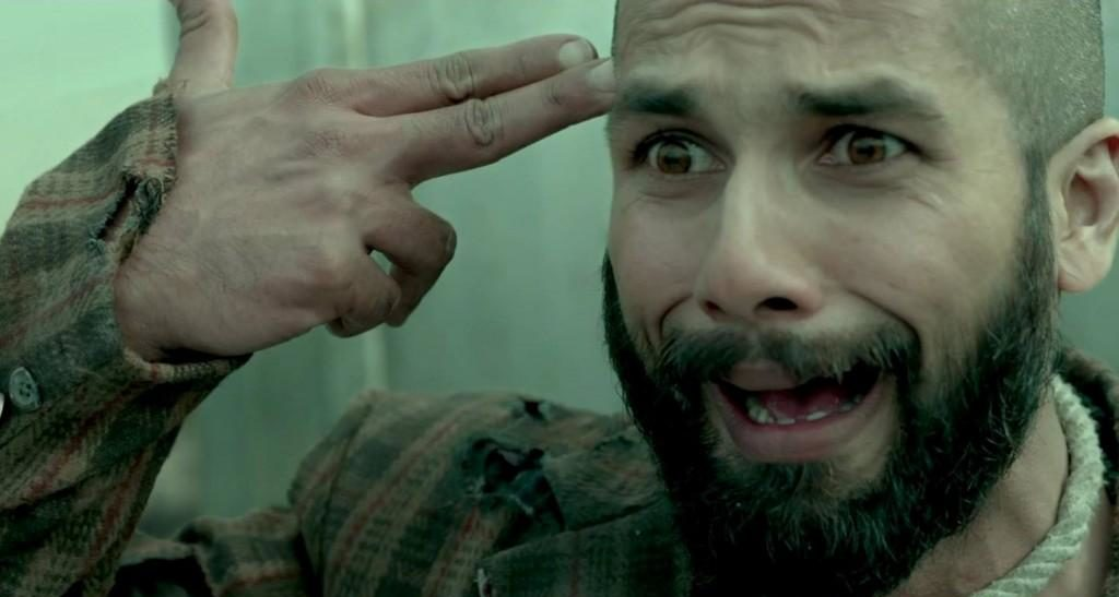 Bollywood Actor Shahid Kapoor has a manic expression on his face as he gestures to his head in the shape of a gun in film 'Haider'.