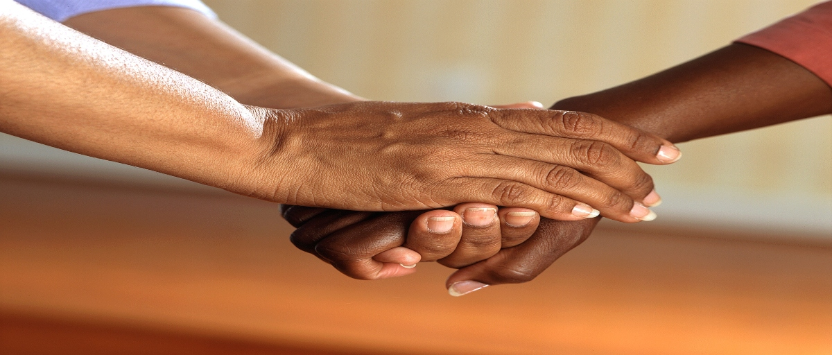 [Image decription: Two hands interlinked with one another.] Via Pixabay