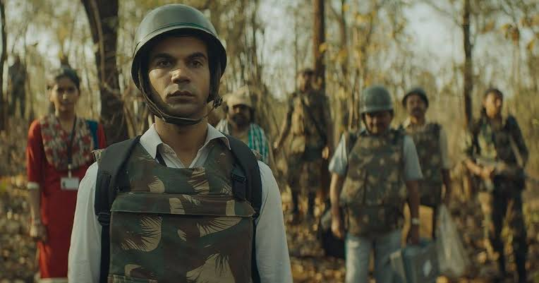 A brown man is wearing an army vest and helmet and looking solemn in Bollywood Film Newton.