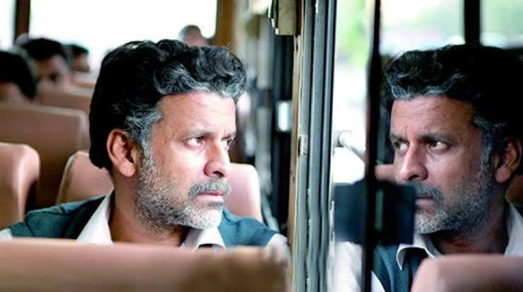 A brown man with graying hair and beard is looking out the window of a bus in Bollywood film 'Aligarh'.