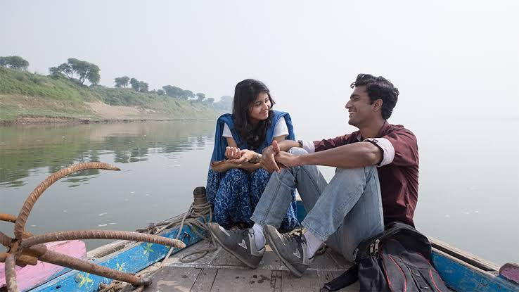 A young girl and guy relaxing on a boat and smiling at each other in Bollywood film 'Masaan'.