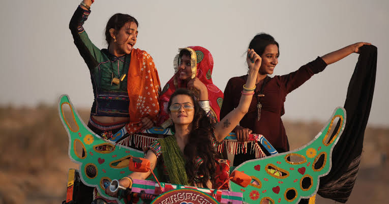 Four female friends wearing ethnic attire are happily riding a tractor in the fields in Bollywood film 'Parched'.
