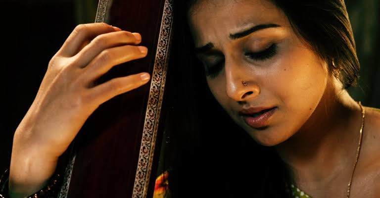 A brown woman is holding a classical instrument with anguish on her face.