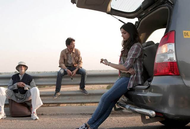A girl is leaning against the open trunk of a parked car with an old man and a young boy sitting in the background.