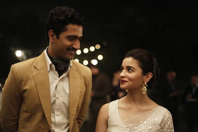 A young Indian couple looking sideways and smiling lovingly at each other in Bollywood Film Raazi.