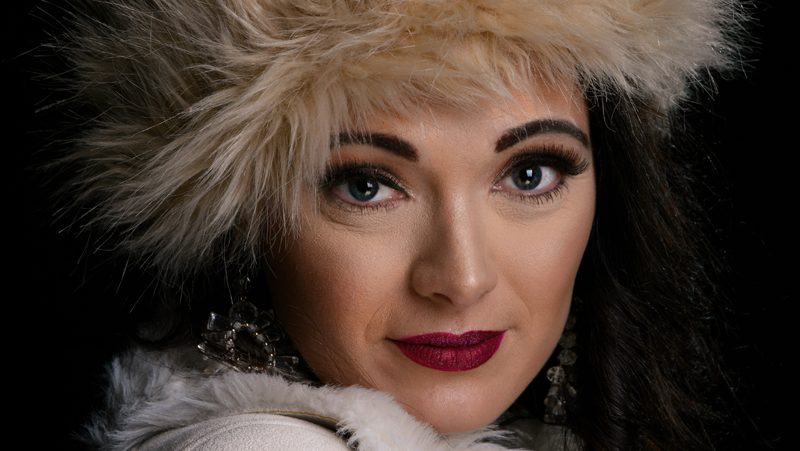 An image of a woman in a fur hat and dark pink lipstick smiling into the camera.