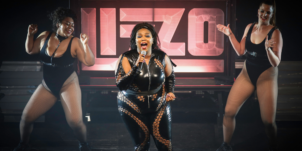 [Image description: Artist Lizzo performing on stage with two dancers by her side]
