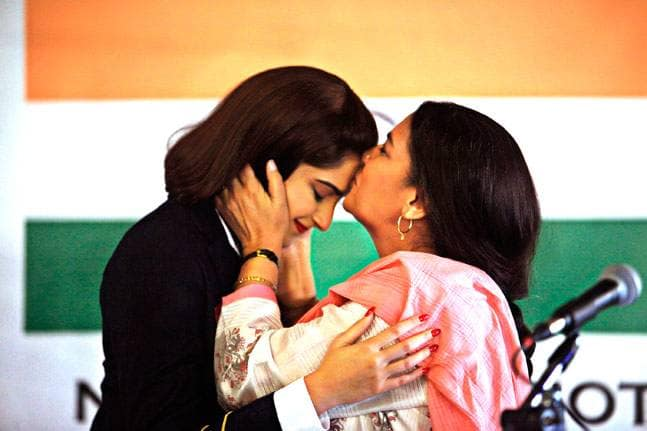 A mother kissing her daughter on the forehead with Indian flag in the background.