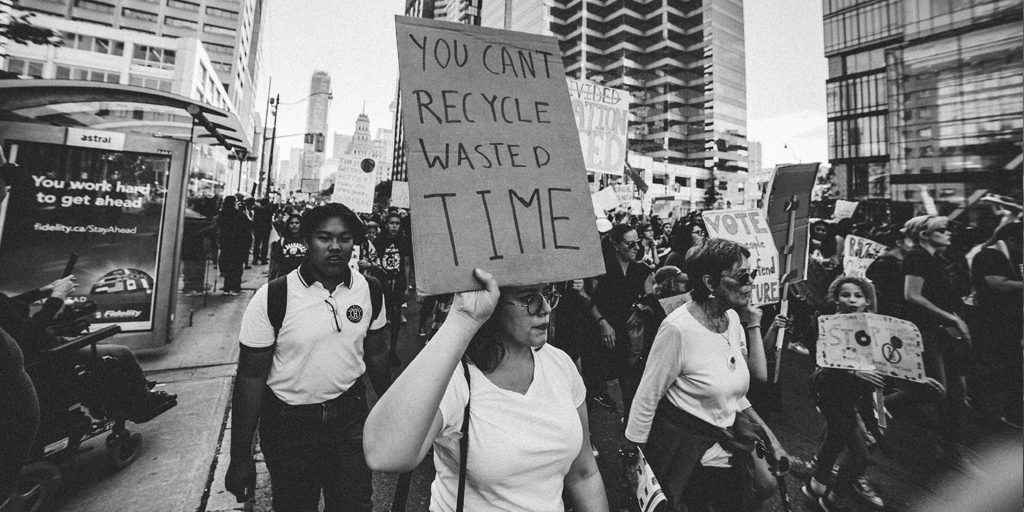 "A black and white image of a protest in a city, with a woman holding up a sign saying, ""You can't recycle wasted time."""