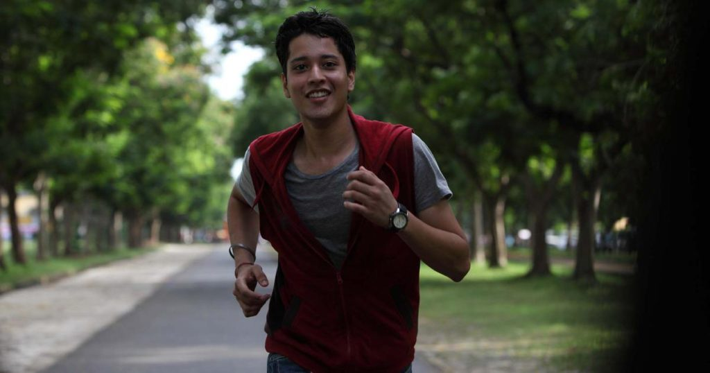 A young man wearing a red sweater is laughing as he runs in Bollywood's 'Udaan'.