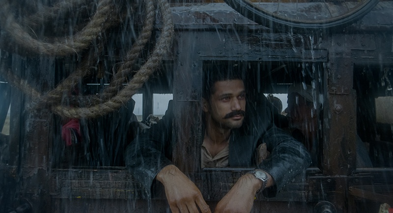 A man with a mustache had his arms hanging out of a train's window as it pours rain in Bollywood film 'Tumbadd'.
