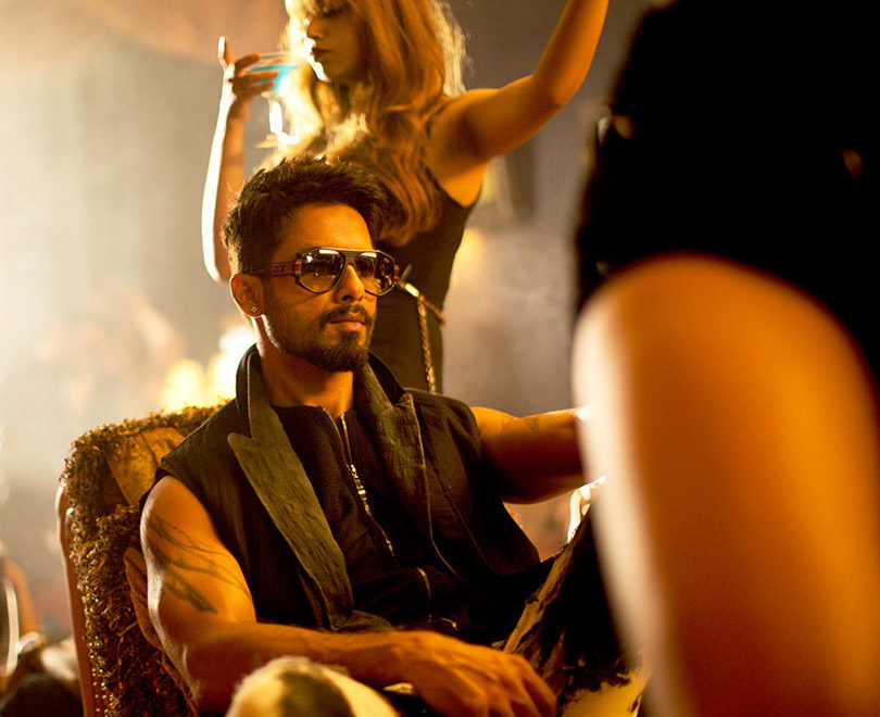 A dark-haired man wearing sleeveless black shirt and sunglasses is sitting around dancing women in a night club.
