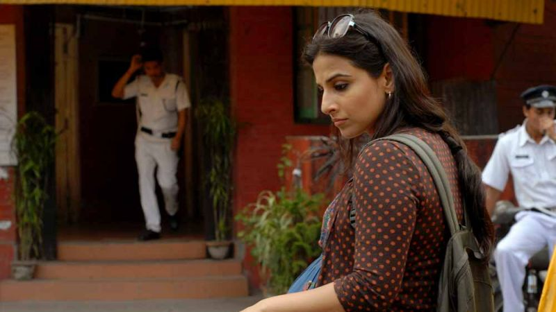 A pregnant Indian woman looking down as a man in white uniform approaches her in Bollywood film 'Kahaani'.