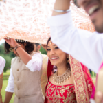 Three men holding a dupatta over a smiling bride, who is wearing a red lehenga.