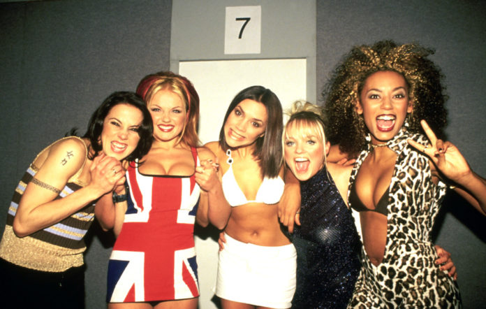 The Spice Girls smile and pose for the camera.