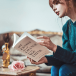 Red-headed woman in a teal sweater sitting on an armchair reading a book.