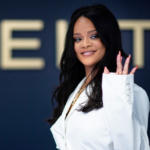 Rihanna wears a white dress and waves at the camera. A poster behind her displays the word 'FENTY'.