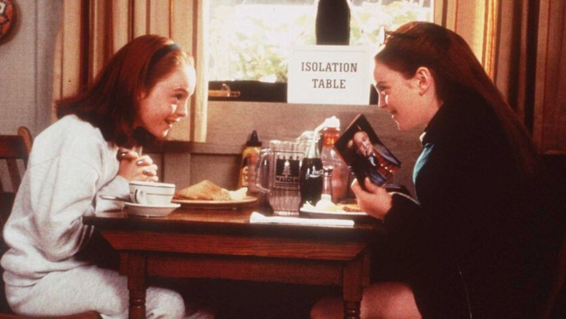 "[Image description: Two red-headed girls sit at a table labeled ""Isolation Table,"" leaning toward each other and smiling. One is holding a photo of an older man.] Via The Parent Trap on IMDb"