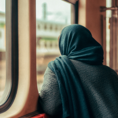 [Image description: Woman wearing a scarf sits, staring out the window.] via Unsplash