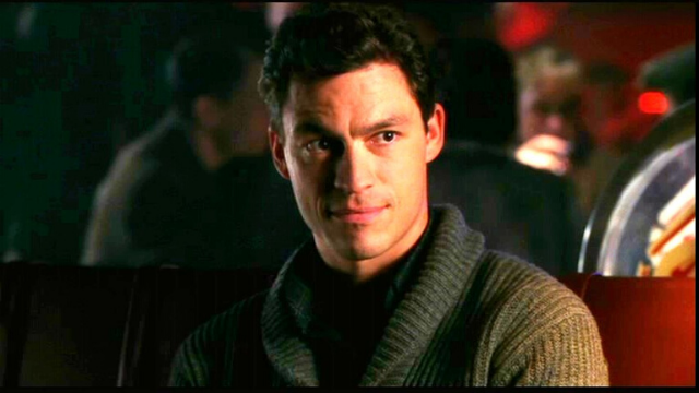 A man with brown hair wearing a dark green sweater looks to the side.