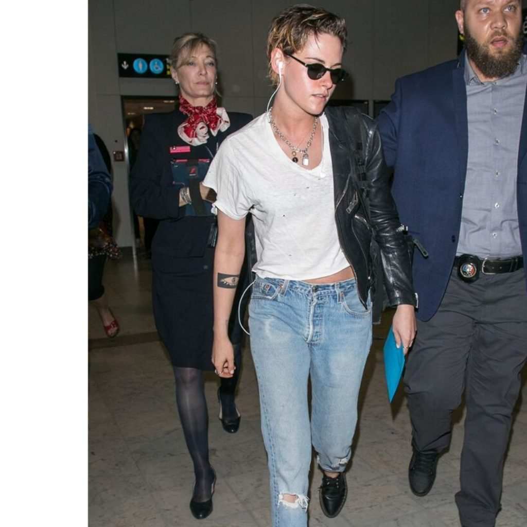 Kristen Stewart wearing a plain white t-shirt, torn jeans, a leather jacket, and a simple chain necklace.