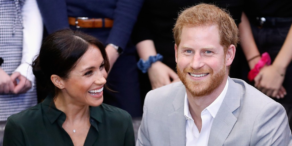 Meghan Markle is sat next to her husband, Prince Harry. She is smiling at him and he is smiling at the camera