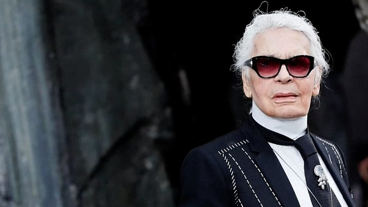 Karl Lagerfeld wears a black suit and sunglasses and looks towards the camera.
