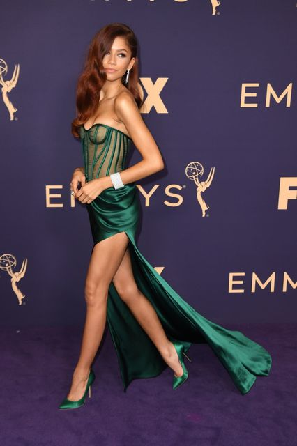 Zendaya wears an emerald-green strapless dress with a thigh-high slit. Her hair is dyed red.