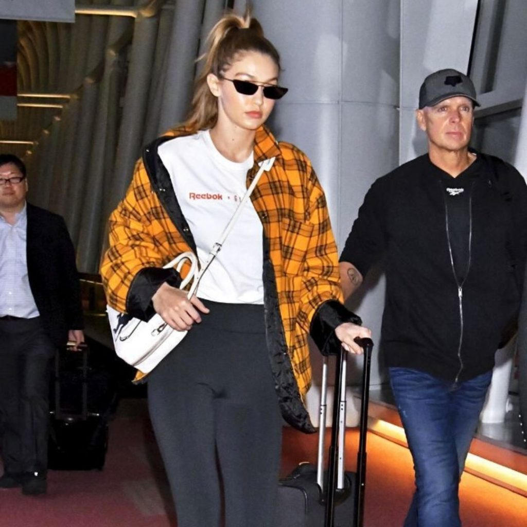 Gigi Hadid wearing black leggings, a white t-shirt, and an orange plaid jacket at an airport.