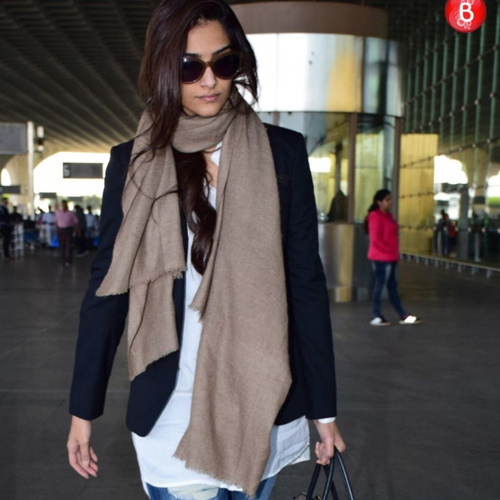 Actress Sonam Kapoor wearing a plain white t-shirt, a jacket, a scarf and jeans at the airport.