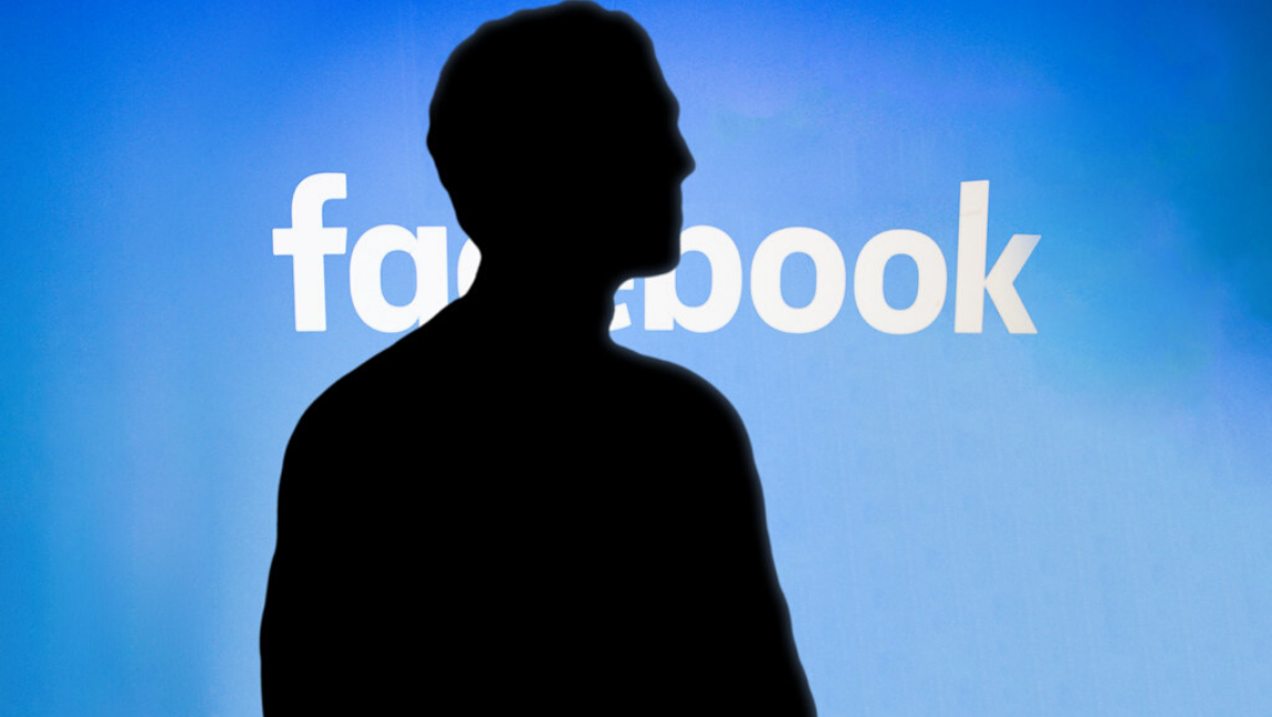 "[Image description: Facebook CEO stands in shadow in front of blue screen with the word ""Facebook.""] via Wikimedia Commons"