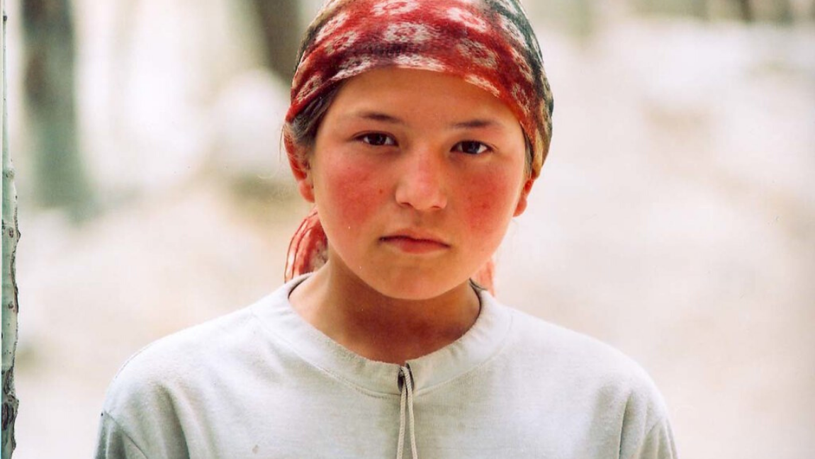 [Image description: Uyghur girl looks directly at the viewer, scarf tied around her hair.] via Flickr