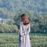 [Image description: Woman in a flowing dress looks out at a field.] via Unsplash