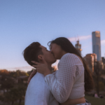 [Image Description: Man and woman kissing with a city in the background]