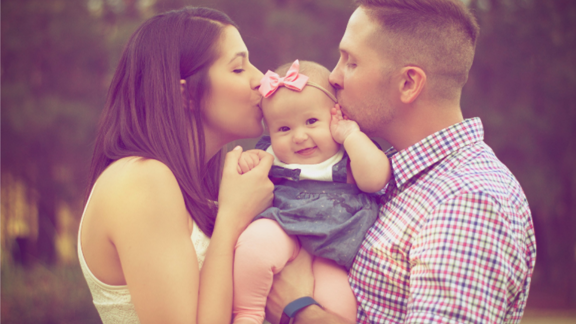 A woman and man kissing a baby.